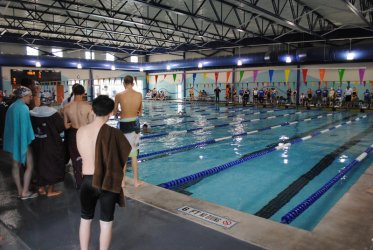 students standing by indoor swimming pool
